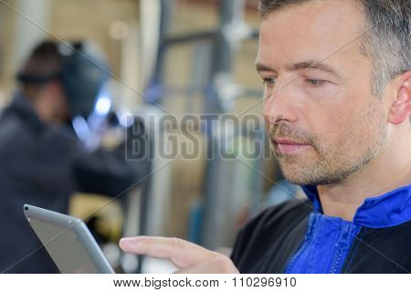 Closeup of workman using tablet