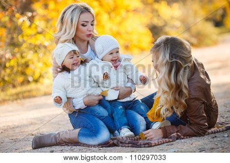 Moms and kids for a walk in the park in autumn