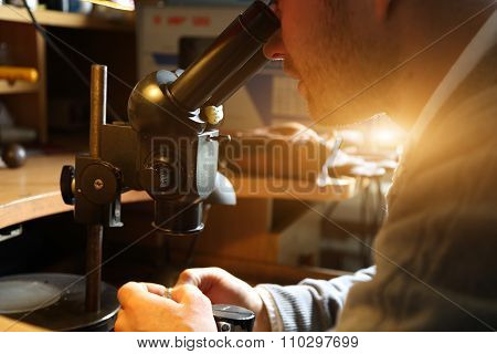 Jeweler looking at the ring through microscope