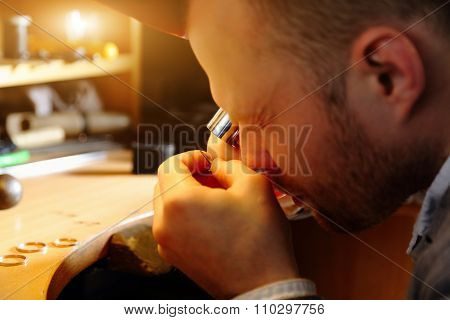 Jeweler looking at the tool through magnifying glass