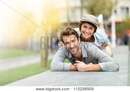 Girl on boyfriend's back laying on public bench