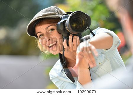 Young woman photographer doing a photo shoot with model