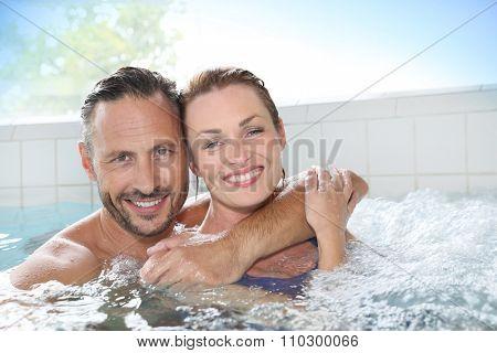 Couple enjoying hot tub bath in spa center