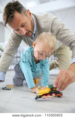 Daddy and baby boy playing with toys on the floor