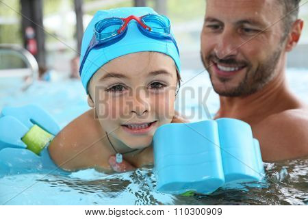 Little boy learning how to swim
