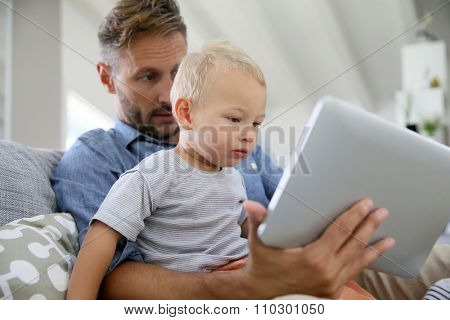 Daddy and baby boy playing with digital tablet
