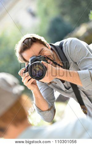 Photographer taking picture of trendy model in park