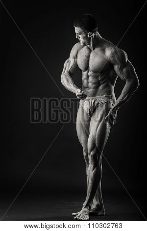A man shows his muscles on dark background