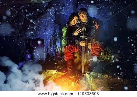Medieval King In Armor With Sword Is Sitting On Furs Near The Camp Fire With His Princess. Snow Fall