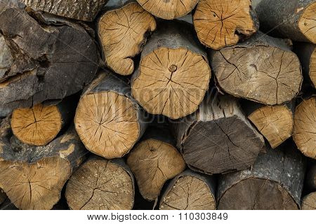 The texture of wood. firewood stacked under the stone wall