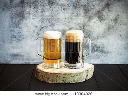 Light and dark beer in mugs on wooden board, grunge backdrop.