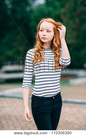 Outdoor Portrait Of Beautiful Girl With Long Curly Red Hair And Green Eyes, touching her ginger hair