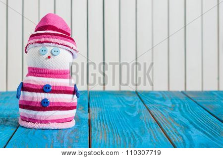Christmas Card with snowman in stripy suit With emty space for text. postcard. Closeup on wooden bac