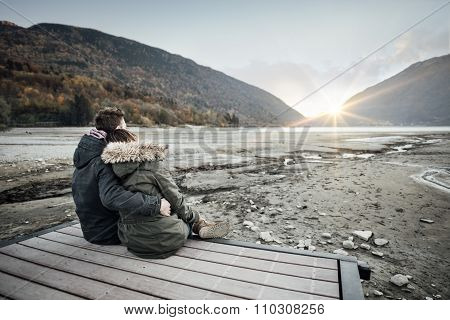 Loving Couple Sitting On A Pier