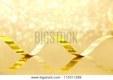 Golden Streamer On Shiny Background. Holiday Background Or Greeting Card. Selective Focus