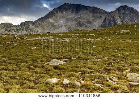 Green meadow and clouds over Kamenitsa peak