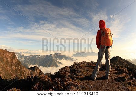 young woman backpacker hiking on mountian peak