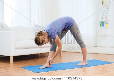 fitness, sport, people and healthy lifestyle concept - woman making yoga intense stretch pose on mat