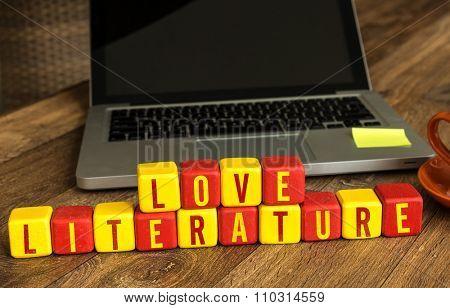 Love Literature written on a wooden cube in a office desk