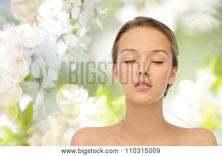 beauty, people, organic, eco and health concept - young woman face with closed eyes and shoulders over green natural background with cherry blossoms