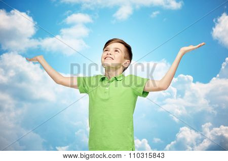 childhood, achievement, gladness and people concept - happy smiling boy in green polo t-shirt raising hands and looking up over blue sky and clouds background