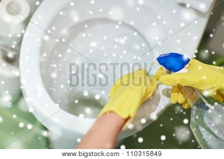 people, housework and housekeeping concept - close up of hand in rubber glove with detergent cleaning toilet pan over snow effect