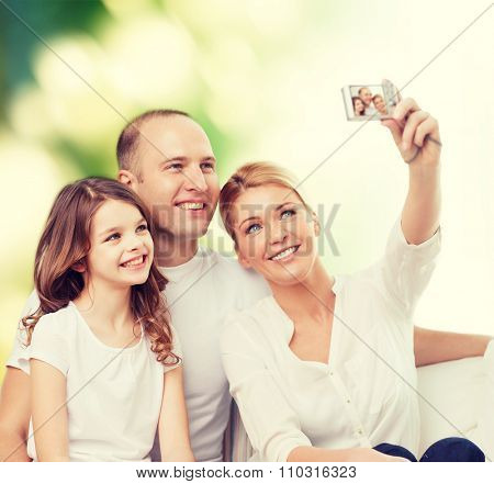 family, technology, ecology and people - smiling mother, father and little girl making selfie with camera over green background
