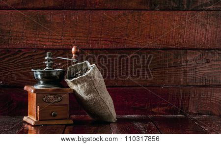 Coffee mill with burlap sack full of roasted coffee beans over wooden vintage table.