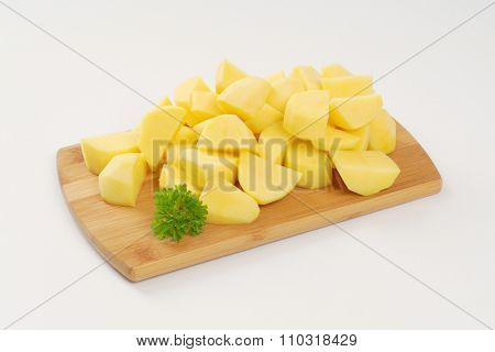 heap of raw diced potatoes on wooden cutting board