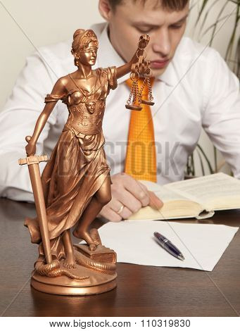 Justice statue and lawyer reading a book in the office