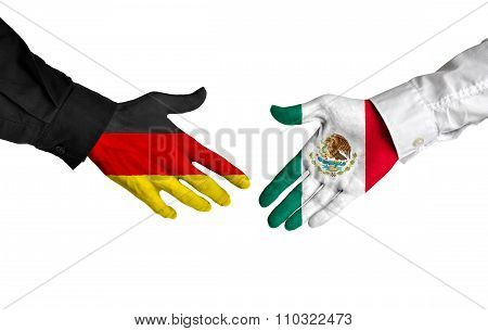 Germany and Mexico leaders shaking hands on a deal agreement