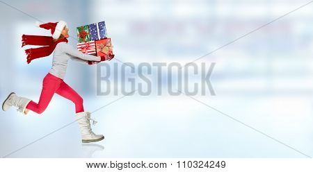 Happy woman with Xmas gifts running over blue background.
