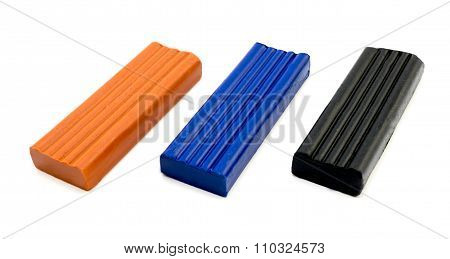 3 Pieces Of Plasticine Orange, Blue And Black Isolated On White