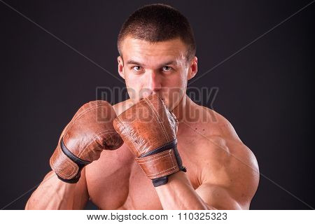 The man in boxing gloves. Young Boxer fighter over black background.