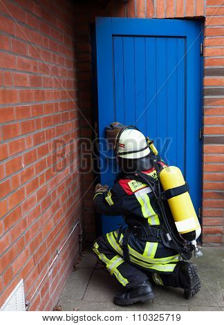 Fireman with breathing apparatus and oxygen bottle opens a door