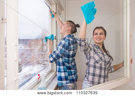 Smiling Young Couple Cleaning Windows