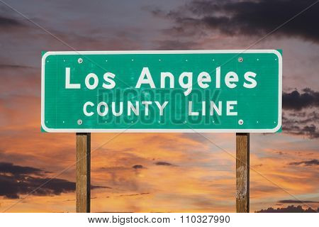 Los Angeles county line sign with sunset sky.