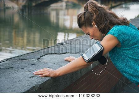 Young Woman In Sportswear And With Mp3 Catching Breath