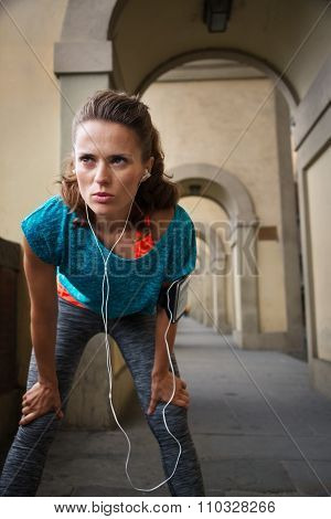 Sporty Woman With Earphones Catching Breath After Jogging