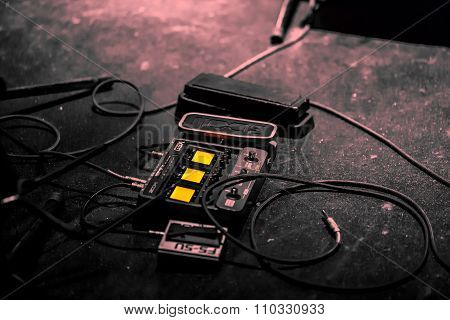 Electric Guitar audio pedal on the floor and cables