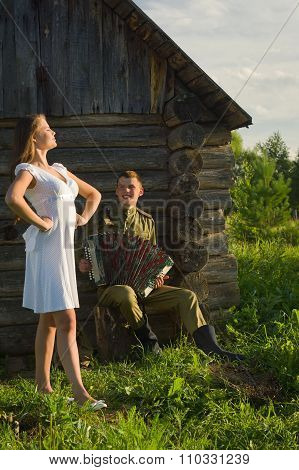 Soviet Soldier In Uniform Of World War Ii Playing Accordion To Girl