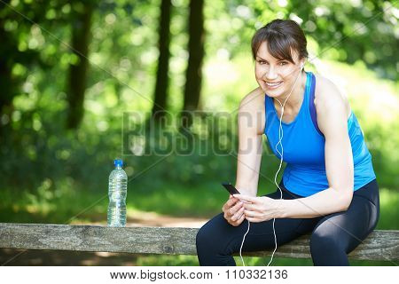 Middle Aged Woman Relaxing With Mp3 Player After Exercise