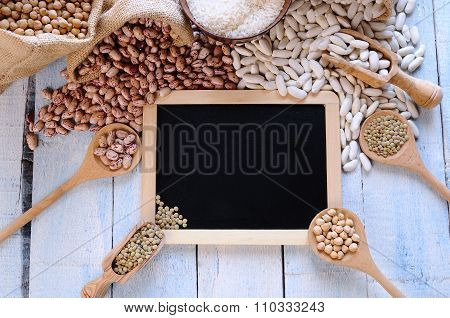 Different Types Of Beans Around Black Framed Square On Blue Wooden Table