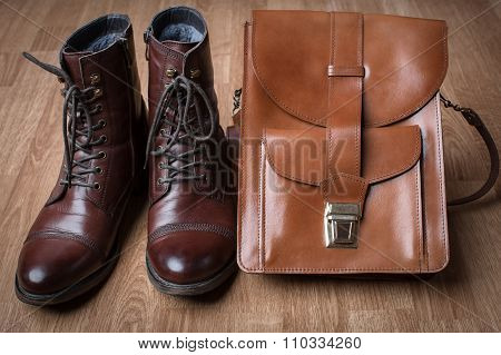 Men's Boots And Brown Bag On Wooden Table