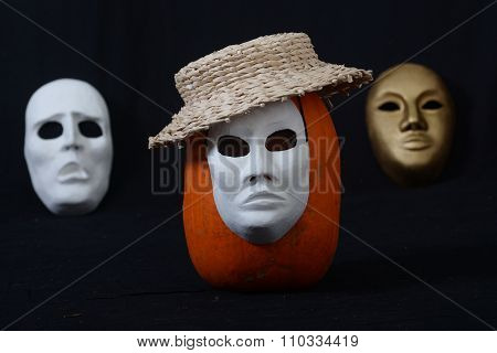 white theatrical mask standing on dark background with pumpkin