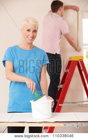 Young Couple Decorating Home Together