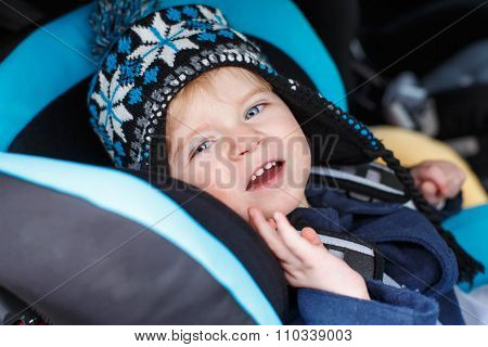 Adorable toddler boy sitting in safety car seat