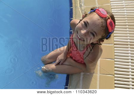 Young Girl Sitting At Swimming Pool