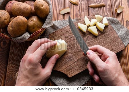 Man Cuts Peeled Potatoes