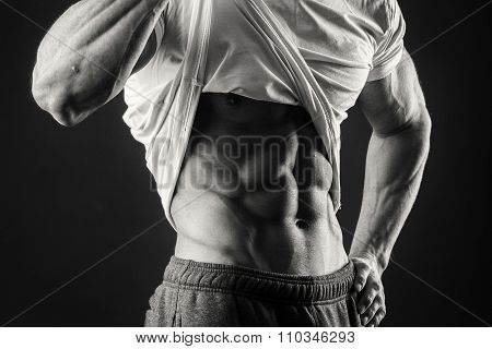 Bodybuilder showing his press. A man shows his abdominal muscles